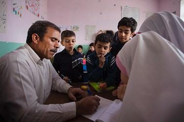 آقا معلم در حال تدریس به کلاس سومیها است،  اینجا به دلیل چند پایه بودن گاهی آموزش به صورت تک تک برای دانشآموزان صورت میگیرد