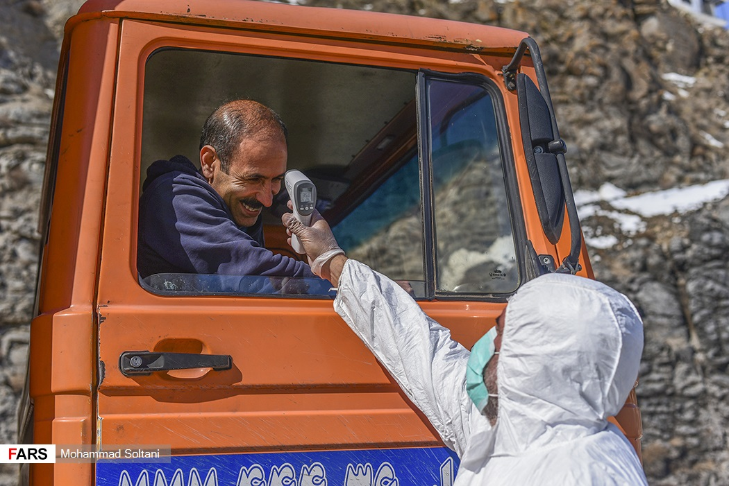 A medical worker checked the temperature of a truck driver in Mazandaran.
