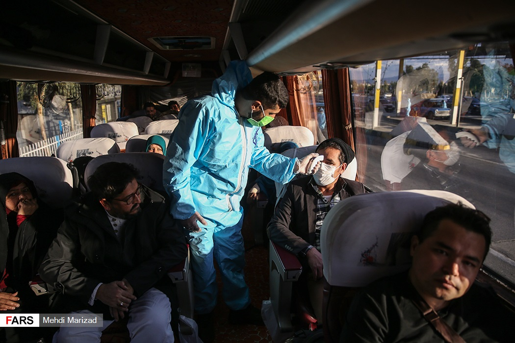 A medical worker checked the temperature of individuals on a bus.