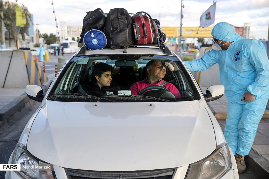 Medical personnel checked the temperatures of individuals at a checkpoint on the Qom-Tehran highway