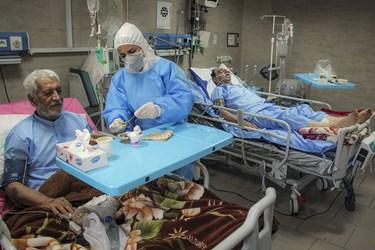 پرستار بخش ویژه کرونای بیمارستان رازی اهواز به بیماران برای خوردن صبحانه کمک می کند.