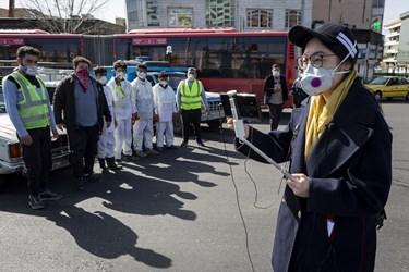 خبرنگارچینی در حال پوشش تصویری عملیات ضدعفونی معابر میدان انقلاب