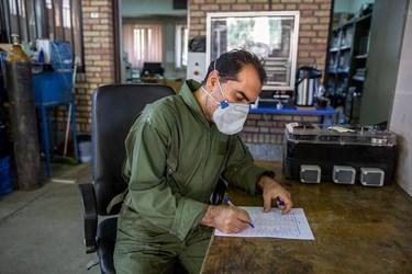 حسین فلاح تکنسین آزمایشگاه عملیات واحد محصولات خارج شده از کارگاه را در لیست یادداشت می کند.