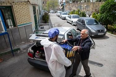 راننده بیمارستان با همکاری نیروی جهادی آبمیوه و آبلیمو عسل تهیه شده را به بیمارستان معین منتقل می کند