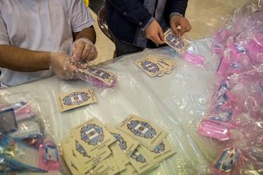 خادمین دعای مخصوص نیمه شعبان را در بسته بندی ها قرار می دهند.