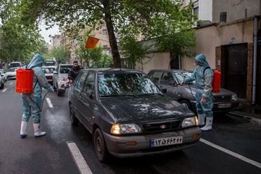 تعدادی از خادمین هیئت مکتب المهدی در حال ضد عفونی کردن خودرو های عبوری در محدوده میدان شهدا