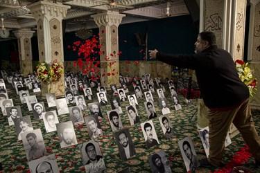 گل افشانی قاب عکس شهدا در حسینیه امامزاده