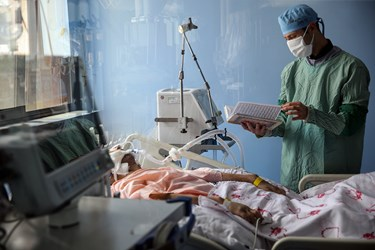 جزخوانی قرآن توسط یکی از پرستاران بر بالین بیمار مبتلا به کرونا در بخش ایزوله