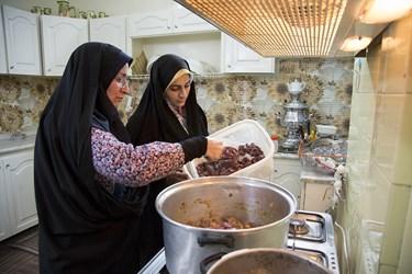 اعضای گروه جهادی فتح، معصومه پاپی نژاد و فائزه مسعودی در حال پخت غذا