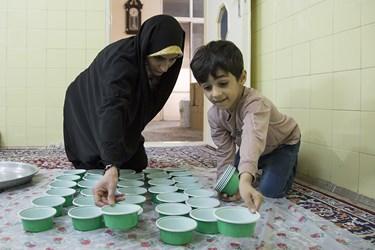 حسین به خواهرش فائزه مسعودی در آماده سازی ظروف کمک میکند