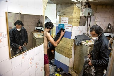 افراد بیخانمان پس از ورود به گرمابه، لباسهای خود را درآورده و برای شستشوی سر و گردن آماده میشوند.
