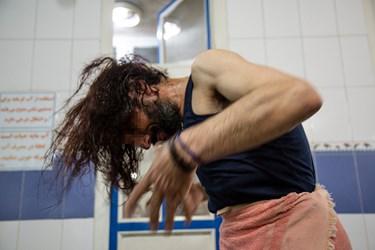 یکی از بیخانمانها پس از استحمام، موهای خود را خشک میکند.