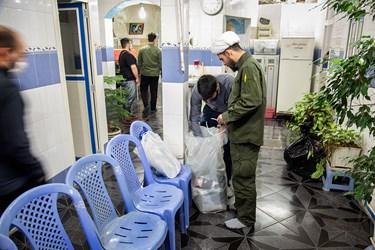 حجتالاسلام اسدی و یکی از افراد گروه، برای بیخانمانها لباسهای اهدایی را آماده میکنند.