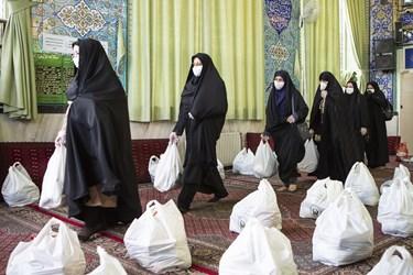 جمعآوری بسته های معیشتی جهت توزیع به خانواده های کمبرخوردار توسط بانوان مددکار کمیته امدا امام خمینی (ره)