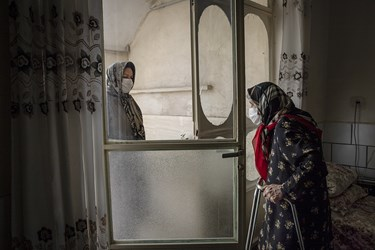 همسایه های مادر بزرگ که قبل از شیوع ویروس کرونا هر روزبه او سر می زدند،در دوران قرنطینه فقط چند دقیقه از بیرون خانه کنار پنجره با او احوالپرسی میکنند.