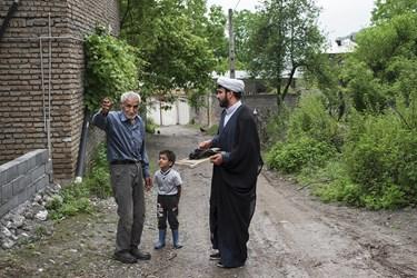 حجت الاسلام خرم دل در حال رفتن برای سرکشی به کندوهای زنبور عسل  با یکی از اهالی خوش و بش می کند