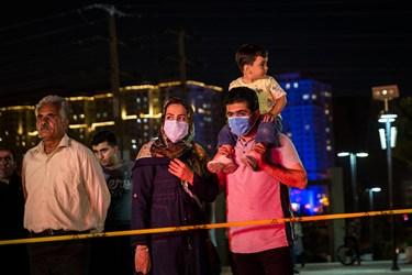 يك خانواده به دليل شيوع كرونا  با ماسك های بهداشتی در آئين رونمايی از سامانه پدافندي سوم خرداد حضور پيدا كرده اند/درياچه شهدای خليج فارس