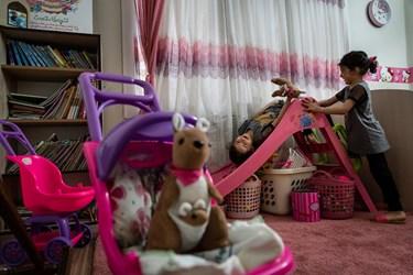ریحانه و فاطمه در حال بازی در اتاقشان هستند.به دلیل شاغل بودن مادر، تنها ساعاتی در روز را در منزل خودشان سپری می کنند.