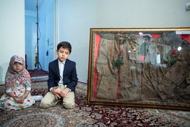 فرزندان شهید الله کرم در کنار لباس پدر