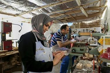 خانم خدیجه جوادزاده  در حال پولیش زدن اسباببازیهایی که همسرشان تولید کرده است.