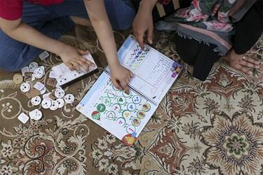 خانم خدیجه جوادزاده با سنا دختر بزرگش در حال تمرین درس ریاضی با استفاده از وسایلی است که در کارگاه خود تولید کردهاند.