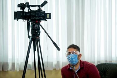 یکی از تصویربرداران حاضر در محل نشست خبری از عینک محافظ چشم جهت مقابله با ویروس کرونا استفاده میکند