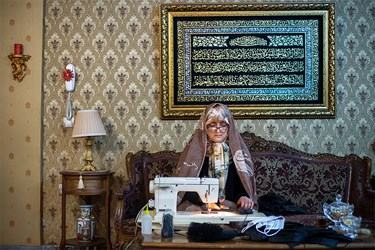 خانم جمیله جعفری یکی از خیاطهای داوطلب است که پارچه و کِشهای ارسالی از مسجد را تبدیل به ماسک میکند.