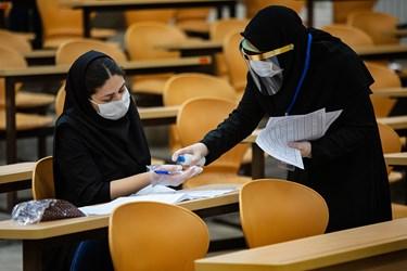 استفاده از اسپری ضدعفونی کننده توسط داوطلب  آزمون دکتری سال 99 در دانشگاه شریف