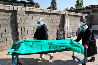 خواهران طلبه متوفای کرونا غسل داده شده را به سردخانه انتقال می دهند.