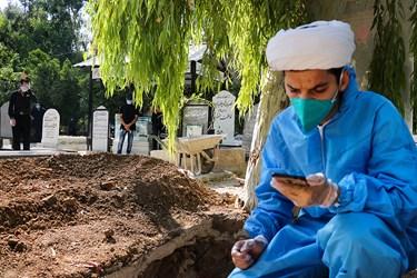 طلبه جهادی مجید ایمنی بالای سر متوفای کرونا تلقین می خواند.