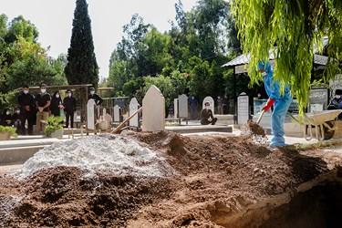 ریختن خاک مخلوط با آهک درون قبر توسط کارگر دارالرحمه شیراز