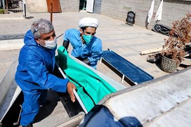 علمدار سی سختی (چپ) و طلبه جهادی مجید ایمنی (راست)  متوفای کرونا را درون آمبولانس می گذارند.