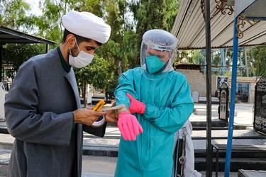 از سمت راست: محمدجواد بازیار، طلبه جهادی ساسان نظری جهت جلوگیری از نفوذ آب به درون دستکش  دور آن چسب می زند.