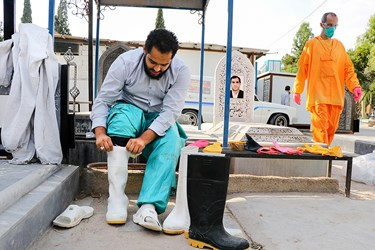 طلبه جهادی امیر حسین عباسی خود را برای شروع به کار غسل و کفن متوفای کرونا آماده می کند.