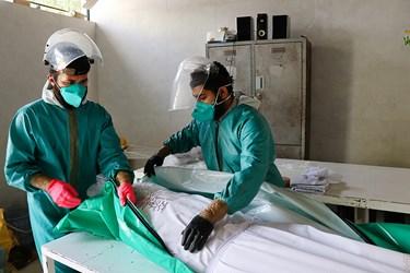 از سمت راست: طلبه جهادی امیر حسین عباسی و محمدجواد بازیار جسد متوفای کرونا را کاور می کنند.