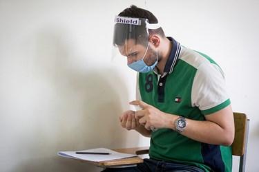 یکی از داوطلبان دستان خود را جهت مقابله با ویروس کرونا ضد عفونی میکند