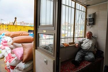 آقای سعادتی یکی از پیشکسوتان بازار علافان در حال استراحت در مغازه خودش هست. او می گوید امسال نسبت به سال های قبل بازارخرید و فروش تعریف چندانی نداشته است. در سالهای اخیر حدود ۲۰۰ تا ۳۰۰ تن غلات و حبوبات خرید و فروش میشد.