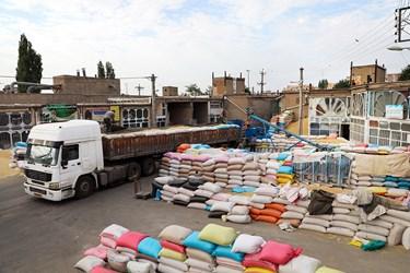 بارگیری گندم به ماشین تریلی برای انتقال به سیلو / مغازه داران بنگاه علافان اردبیل خریدهای خرد خود را جمع آوری کرده و به صورت یکجا با ماشین تریلی به سیلوها انتقال داده و به استان های دیگر ارسال میکنند.