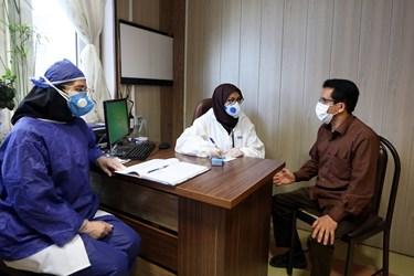 دکترترکمان با رعایت پروتکل بهداشتی در حال کسب اطلاع از حال عمومی بیمار و معاینه او در مطب شخصی خود است