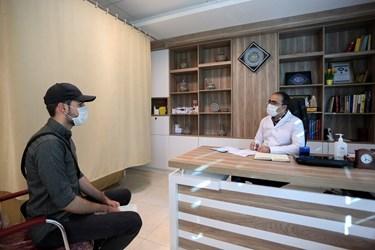 دکتر عالمی با رعایت پروتکل بهداشتی در حال کسب اطلاع از حال عمومی بیمار و معاینه او در مطب شخصی خود است