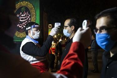 سنجش دمای بدن شرکت کنندگان هنگام ورود به هیئت میثاق با شهدا در دانشگاه افسری امام علی(ع)