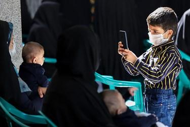 پسربچه ای که با استفاده از ماسک در مراسم روضه شرکت کرده است، از مادر و برادر خود باتلفن همراه عکاسی می کند.