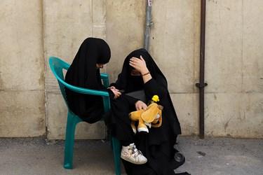 مادری به همراه دختر خرد سالش که در حال بازی با تلفن همراه می باشد، در مراسم روضه دهه اول محرم کوچه عادل منفرد در میدان قیام، شرکت کرده است.