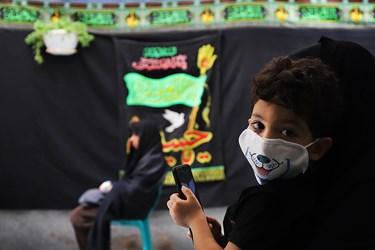 کودکان با استفاده از ماسک در مراسم عزاداری سیدالشهدا در کوچه عادل منفرد شرکت کرده اند.