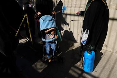 در ورودی کوچه عادل منفرد که در آن مراسم روضه سیدالشهدا با رعایت دستورالعمل های بهداشتی برپاست، یکی از خادمین در حال ضد عفونی کردن کالسکهی کودکی است.
