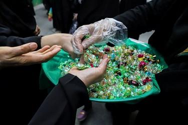 یکی از خادمین در مراسم روضه ای که در کوچه عادل منفرد برپاشده است، بااستفاده از دستکش، شکلاتهای تبرکی را بین بانوان عزادار توزیع میکند.