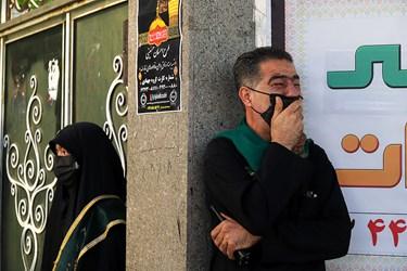 یکی از خادمین مراسم روضه که وظیفه انتظامات رابرعهده دارد در گوشه ای از ورودی کوچه عادل منفرد به روضه گوش میدهد.