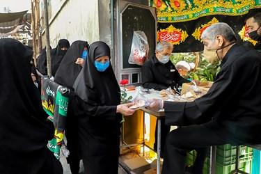 بعد از پایان مراسم روضه، عزاداران با رعایت فاصله اجتماعی و به ترتیب در حال دریافت بسته های تبرکی هستند که خادمین مراسم با رعایت دستورالعمل های بهداشتی آن هارا تهیه نموده اند.