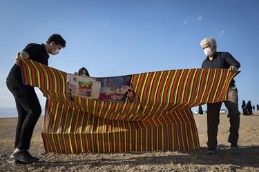 خانوادهها زیراندازهای شخصی را در محوطه محل برگزاری مراسم پهن میکنند