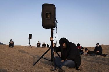 جوانی در عین عزاداری، مراقب است تا باد تجهیزات صوتی را سرنگون نسازد